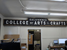 CCAC Broadway entrance gate arch sign, hanging in Facilities Office